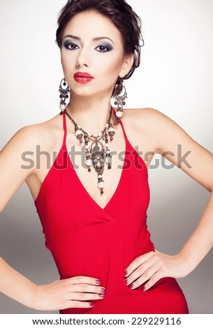 Portrait of young beautiful brunette woman in jewelery standing over white background. Vogue style. Studio shot. - stock photo