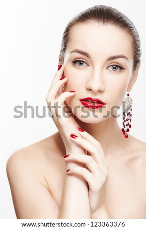 portrait of young beautiful brunette woman in jewelery touching cheek with manicured hand on gray - stock photo