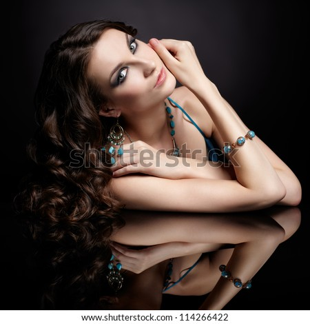 portrait of young beautiful brunette woman in jewellery at black mirror table - stock photo