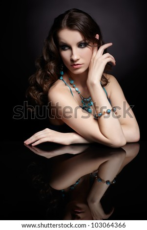 portrait of young beautiful brunette woman in jewellery at mirror table - stock photo