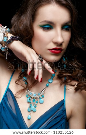 portrait of young beautiful brunette woman in jewellery on black