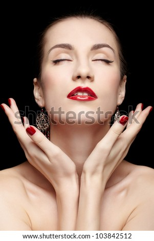 portrait of young beautiful brunette woman in jewellery on black closing eyes - stock photo