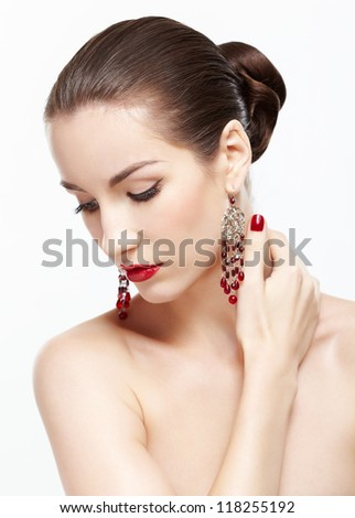 portrait of young beautiful brunette woman in jewellery on gray touching her neck - stock photo