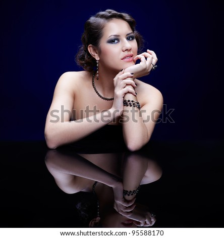 portrait of young beautiful brunette woman in jewelry at mirror table - stock photo