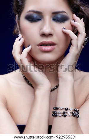 portrait of young beautiful brunette woman in jewelry with manicured fingers touching her face - stock photo