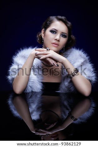 portrait of young beautiful brunette woman in tippet, bracelet, ring and beads at reflecting table - stock photo