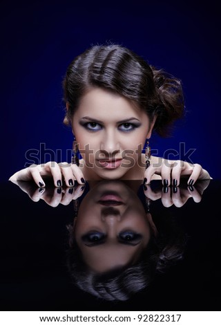 portrait of young beautiful brunette woman putting her manicured fingers on reflecting table - stock photo