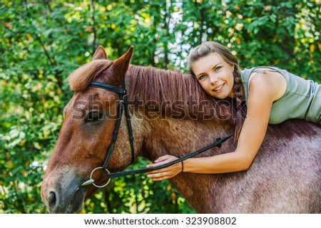 Portrait of young beautiful brunette woman riding horse at summer green forest. - stock photo