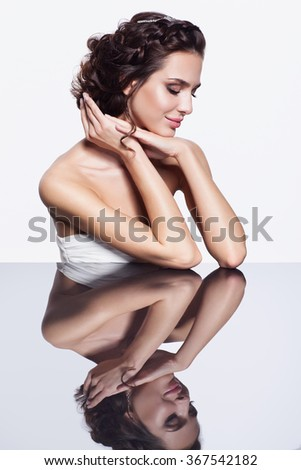 Portrait of young beautiful brunette woman sitting at mirror table on light gray background