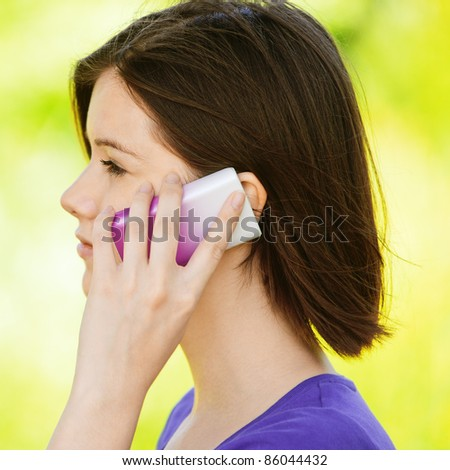 Portrait of young beautiful brunette woman speaking on cellphone at summer green park.