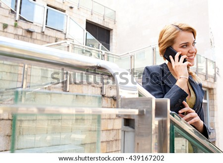 Portrait of young beautiful business woman using a smart phone in financial city, speaking phone call conversation, sunny outdoors. Professional girl using technology, smiling. Lifestyle in exterior. - stock photo