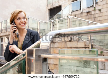 Portrait of young beautiful business woman using a smart phone in stairs financial city, speaking phone call conversation, outdoors. Professional girl using technology, smiling. Lifestyle in exterior. - stock photo