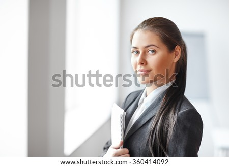 Portrait of young beautiful business woman with documents in the office - stock photo