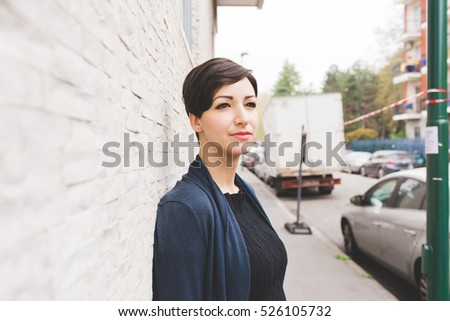 portrait of young beautiful caucasian brown hair woman posing outdoor in the city, looking at camera, pensive - serious, melancholy, serene concept