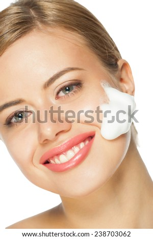 Portrait of young beautiful caucasian woman washing her face. Isolated on white background - stock photo