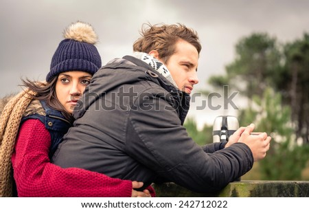 Portrait of young beautiful couple embracing and having hot beverage in a cold day with dark cloudy sky on the background - stock photo