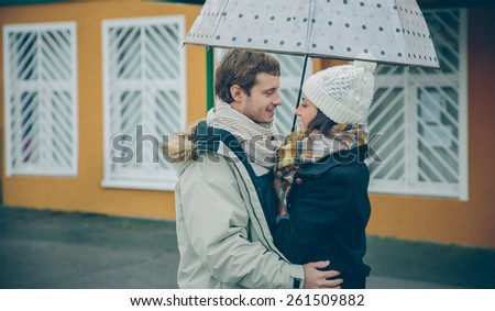 Portrait of young beautiful couple embracing under the umbrella in an autumn rainy day. Love and couple relationships concept. - stock photo