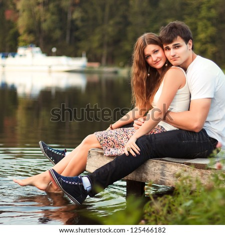 Portrait of young beautiful couple in love sitting near the water - stock photo