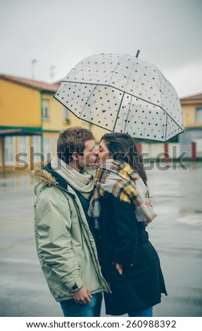 Portrait of young beautiful couple kissing under the umbrella in an autumn rainy day. Love and couple relationships concept. - stock photo