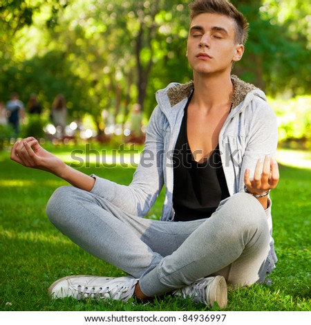 Portrait of young beautiful couple sitting in lotus pose on green grass together, making yoga exercises. Outdoor in summer park under trees