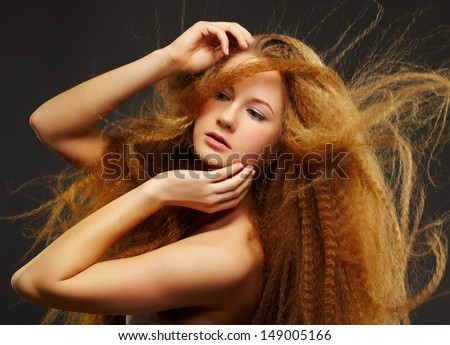 portrait of young beautiful curly redhead woman with waving long hair