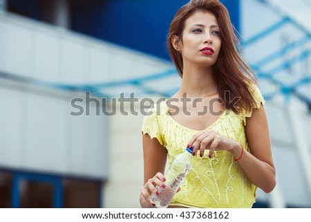 Portrait of young beautiful dark-haired woman wearing trendy knitted vintage t-shirt standing with bottle of water on the street. Modern urban background. Close up. Outdoor shot