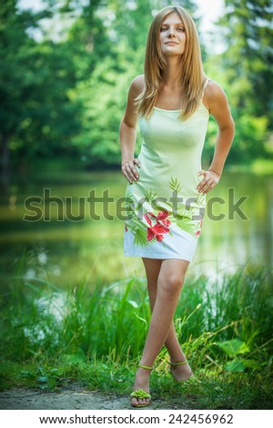 Portrait of young beautiful fair-haired lady at summer green park. - stock photo