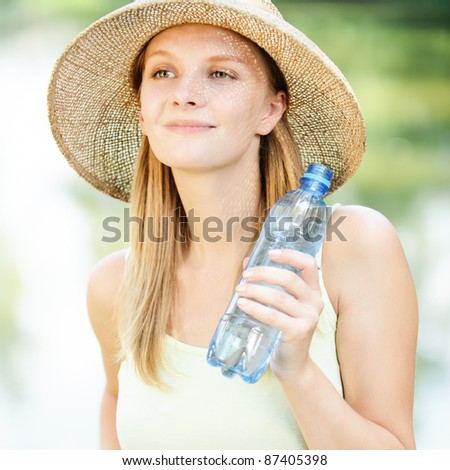 Portrait of young beautiful fair-haired woman wearing straw hat and green dress and holding bottle of water at summer green park. - stock photo