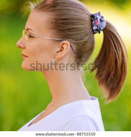 Portrait of young beautiful fair-haired woman wearing white t-shirt and eyeglasses, standing at summer green park. - stock photo