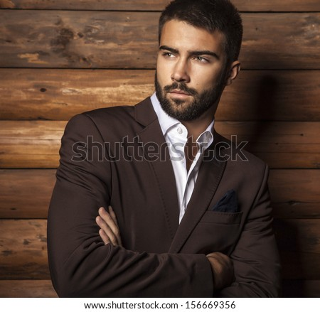 Portrait of young beautiful fashionable man against wooden wall.  - stock photo