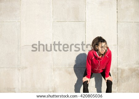 Portrait of young beautiful female leaning on gray background while resting after everyday training. Woman athlete runner taking a break and listening music. Sport active lifestyle concept. Copyspace - stock photo