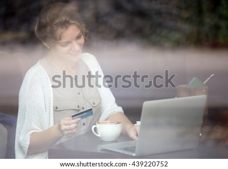 Portrait of young beautiful female sitting in modern urban cafe, drinking coffee and paying with credit card for online shopping on laptop. Shot through window - stock photo