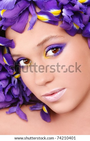 Portrait of young beautiful fresh girl with stylish make-up and irises around her face, selective focus