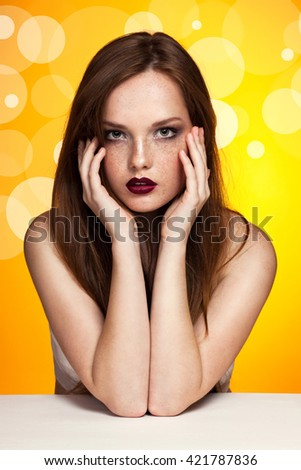 Portrait of young beautiful ginger girl with red lips on a bright yellow background. Sensual bright lips, white skin, passionate look, freckles, long hair. Fashion woman, Vogue. Geometric pattern. - stock photo