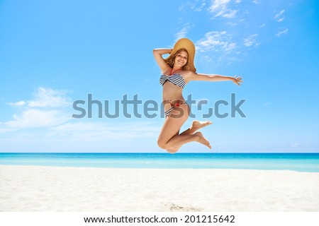 Portrait of young beautiful girl at tropical beach for vacations, jumping mid-air for joy, looking at camera and smiling. Copy space - stock photo