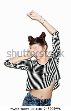 Portrait of young beautiful girl having fun and hiding her face with hand and dancing. Natural makeup and top knot hairdo. White background, not isolated. Inside. - stock photo