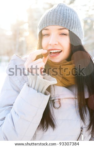Portrait of young beautiful girl having fun outdoors in winter forest and eating tasty chocolate candy