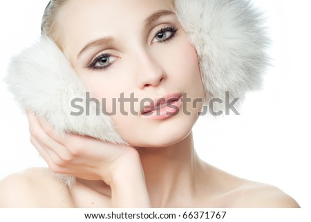 Portrait of young beautiful girl in fur ear muffs - stock photo