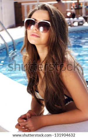 portrait of young beautiful girl in swimming pool - stock photo