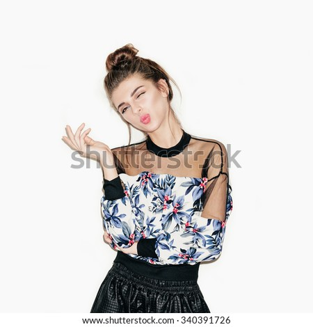 Portrait of young beautiful girl posing for camera. Bright makeup, top knot hairdo and casual style. White background, not isolated. Inside. - stock photo