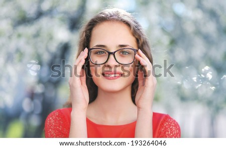 Portrait of young beautiful happy girl in glasses outdoors, nature, youth, student - concept - stock photo