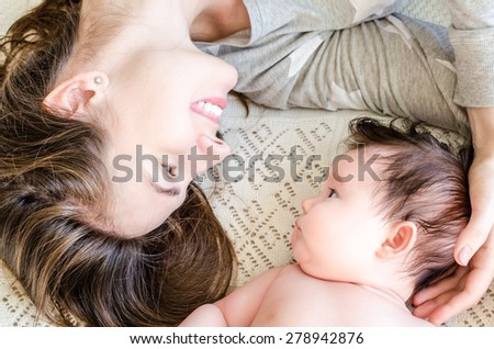 Portrait of young beautiful happy mother with black brunette hair and cute little newborn baby girl lying on woolen blanket on the bed at home. Mother holding her baby's head gently with love.   - stock photo