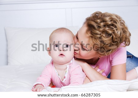 Portrait of young beautiful mather kissing attractive baby lying on bed in the bedroom - stock photo