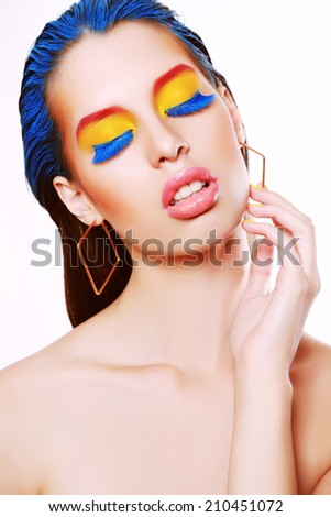 Portrait of young beautiful model with creative make-up, yellow eyeshadows and long false blue eyelashes.