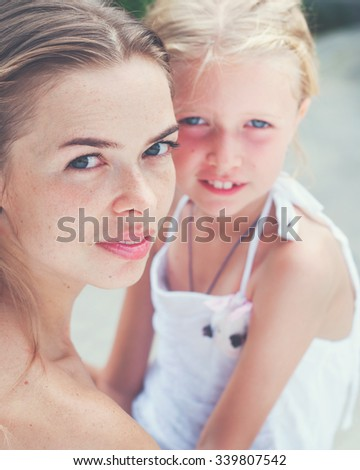 Portrait of Young Beautiful Mother near with Teenager Daughter. Look in the camera. Toned - stock photo