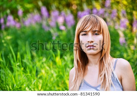 Portrait of young beautiful pensive blond woman at summer green park. - stock photo
