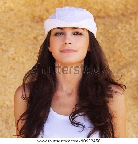 Portrait of young beautiful positive brunette woman wearing white cap, white t-shirt against yellow background. - stock photo