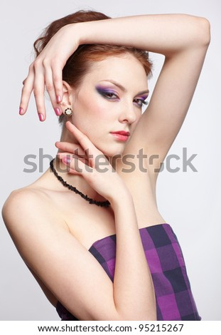 portrait of young beautiful redhead woman in violet dress, beads and ear-rings touching her face with hands - stock photo