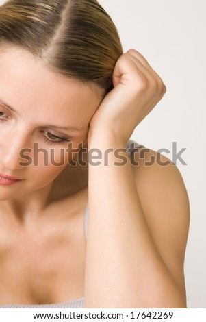 Portrait of young beautiful sad woman on white background