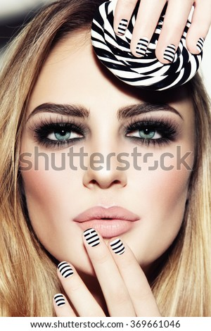 Portrait of young beautiful sexy girl with smoky eyes and stylish striped manicure